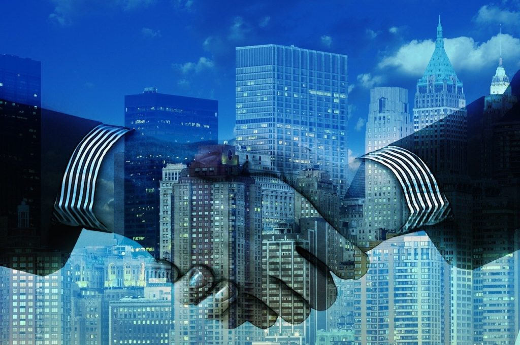 Stylized M&A transaction handshake in front of high rise buildings