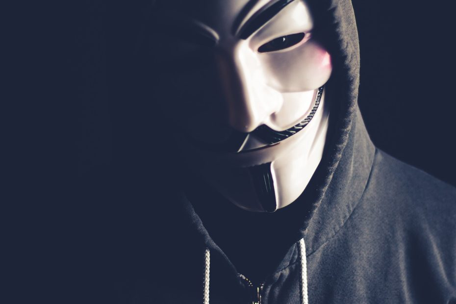 Anonymous hacker with Guy Fawkes mask looking into the camera. Cyber attack threat, remember the fifth of November!